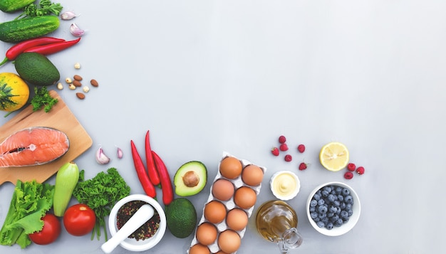Plat leggen met verschillende soorten voedsel, biologische groenten, biologisch fruit, bessen, noten, specerijen, kruiden, olijfolie, kippeneieren en een kopje zalmvis. kopieer ruimte voor wat tekst. grijze betonnen achtergrond