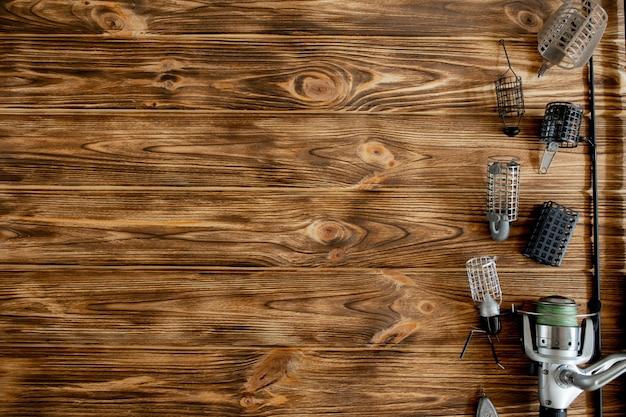 Plat leggen met visgerei, hengel en plastic doos met visgerei en haken, feeders op houten planken, kopie ruimte