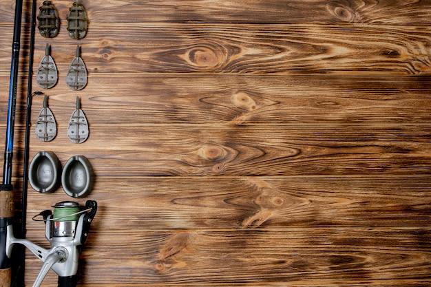Plat leggen met visgerei, hengel en plastic doos met visgerei en haken, feeders op houten planken, kopieerruimte