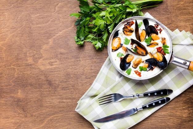 Plat leggen mosselen in witte saus op tafelkleed met copyspace