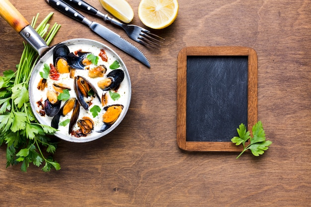 Plat leggen mosselen in witte saus op tafelkleed met schoolbord