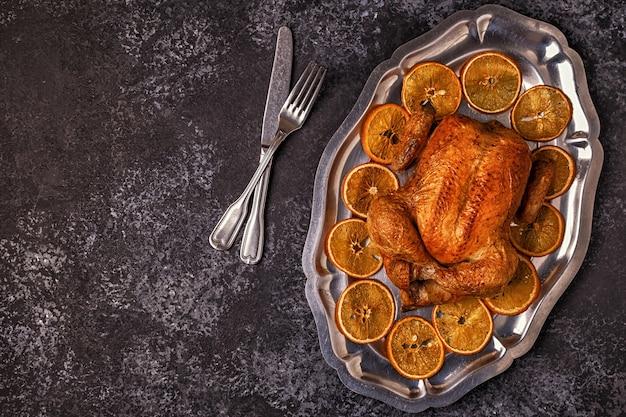 Plat leggen op geroosterde hele kip met stukjes sinaasappel