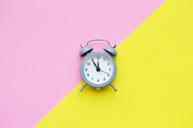 Plat leggen samenstelling van grijze mini wekker. kopieer ruimte, roze en gele achtergrond.