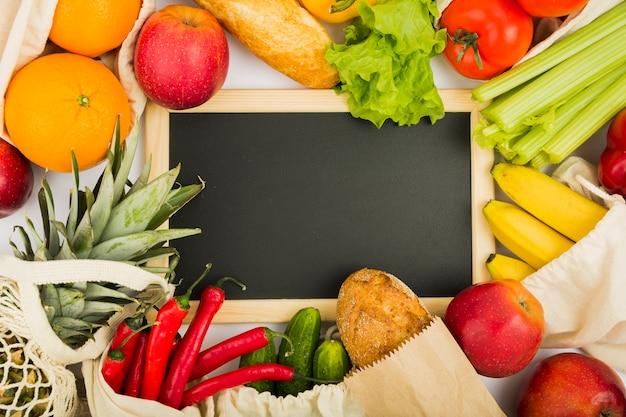 Plat leggen schoolbord met groenten en fruit in herbruikbare tassen
