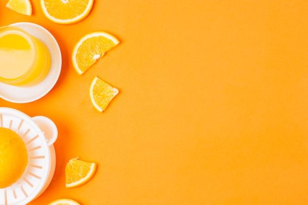 Plat leggen sinaasappelsap op oranje achtergrond met kopie ruimte