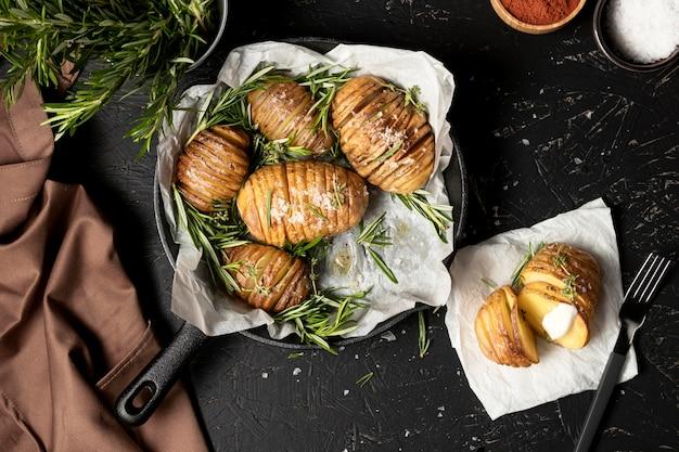 Plat leggen van aardappelen in pan met rozemarijn en andere kruiden