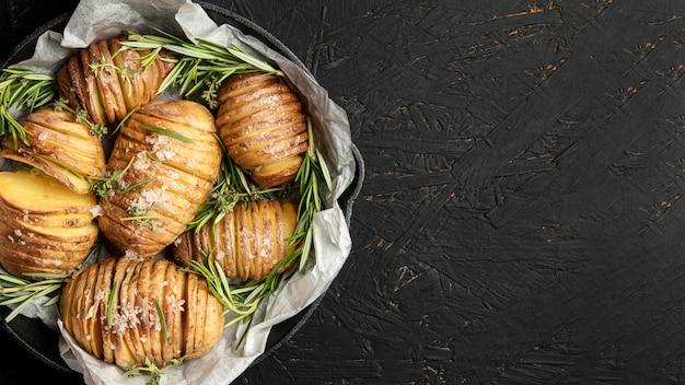 Plat leggen van aardappelen in pan met rozemarijn en kopie ruimte