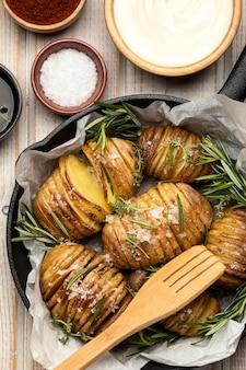 Plat leggen van aardappelen in pan met rozemarijn en kruiden