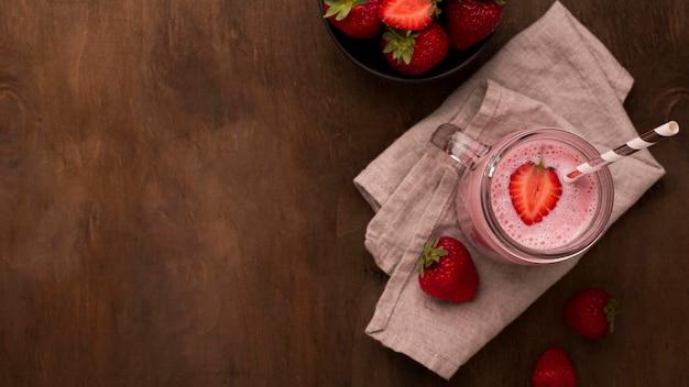 Plat leggen van aardbei milkshake met stro en kopieer de ruimte