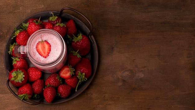 Plat leggen van aardbeienmilkshake met fruit en kopie ruimte
