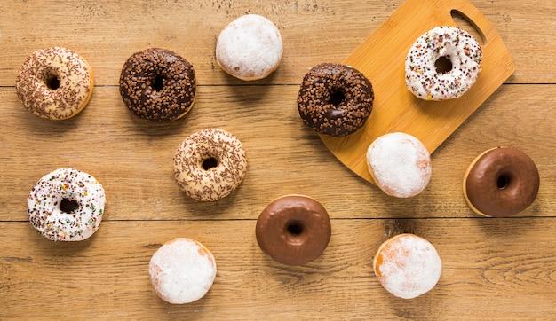 Plat leggen van assortiment van donut op houten oppervlak