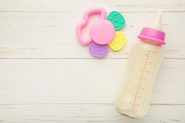 Plat leggen van babymelk met speelgoed op witte achtergrond