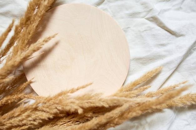 Plat leggen van beige riet pampa gras op de achtergrond van het witte linnen tafellaken