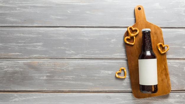 Plat leggen van bierfles met pretzels en kopie ruimte