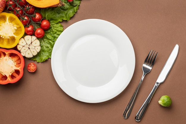 Plat leggen van biologische groenten met bord en bestek