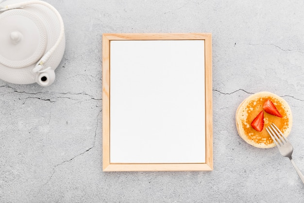 Plat leggen van blanco menu papier met pannenkoeken en theepot