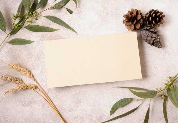 Plat leggen van blanco papier met dennenappels en herfstbladeren