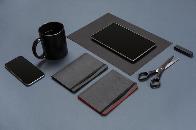 Plat leggen van blanco zwart vel papier, zwarte briefpapier en koffiekopje op grijze desktop mock-up