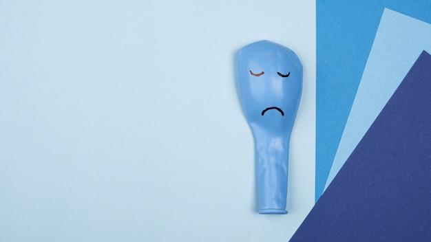 Plat leggen van blauw maandag papier met kopie ruimte en trieste ballon