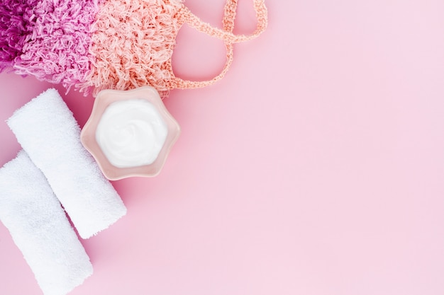 Plat leggen van body butter op roze achtergrond met kopie ruimte