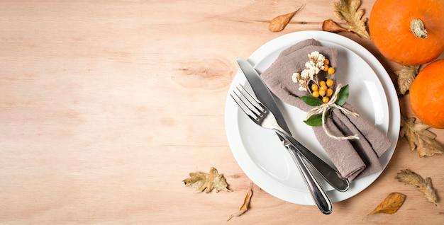 Plat leggen van borden voor thanksgiving-diner met bestek en kopie ruimte