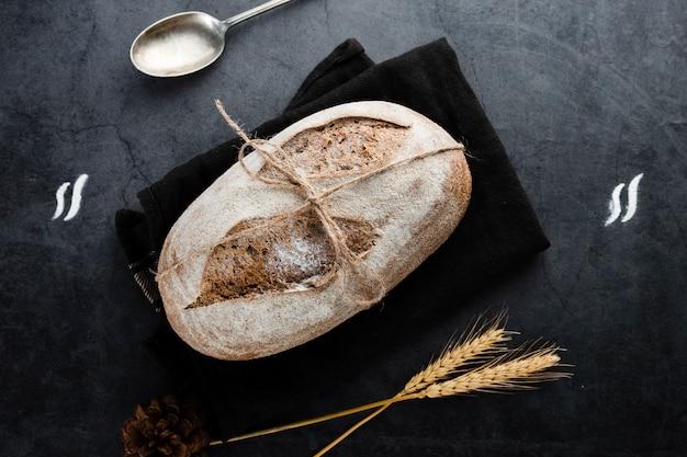 Plat leggen van brood en tarwe op zwarte achtergrond