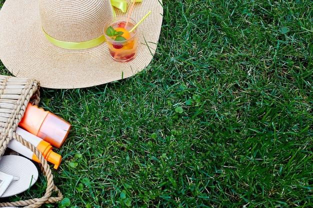 Plat leggen van buiten heldere zomervakantie of reizen lifestyle concept met strozak, hoed, slippers, limonade en zonnebrandspray op grasachtergrond, bovenaanzicht, kopieerruimte.