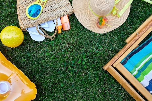 Plat leggen van buiten heldere zomervakantie of reizen lifestyle concept met strozak hoed slippers limonade opblaasbare gele matras en bal zonnebril en zonnebrandcrème spray op gras