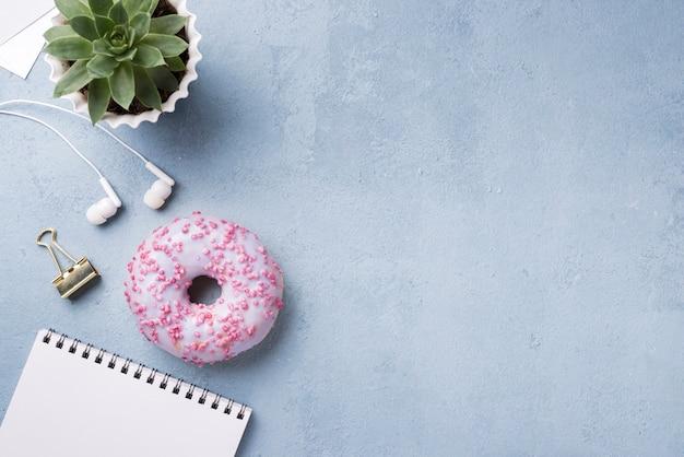Plat leggen van bureau met donut en laptop
