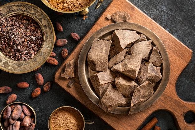 Plat leggen van chocolade met cacaobonen en poeder