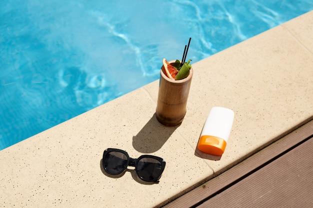 Plat leggen van cocktail in houten container, zwarte modieuze zonnebril en zonnebrandcrème in witte fles, samenstelling voor rust tijdens vakantie. dingen zijn gelegen nabij zwembad.
