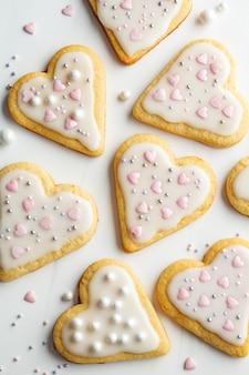 Plat leggen van cookies harten met ijsvorming en ingericht voor valentijnsdag, witte achtergrond. valentijnsdag concept.