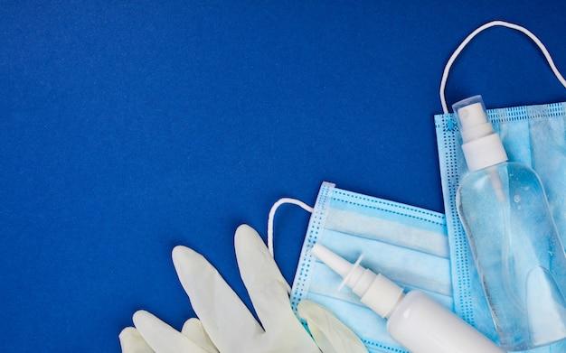 Plat leggen van coronavirus-bescherming, medische beschermende maskers, handschoenen, flessen met handdesinfecterend middel, antiseptisch, desinfectie, spray op blauwe achtergrond, kopie ruimte