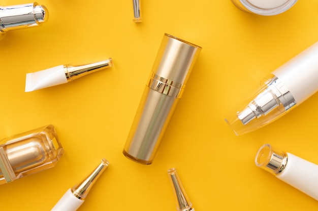 Plat leggen van cosmetische producten ingesteld op gele achtergrond