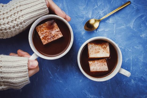 Plat leggen van de handen van de vrouw in een trui en twee kopjes cacao of warme chocolademelk met zelfgemaakte veganistische marshmallow