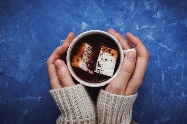 Plat leggen van de handen van de vrouw in een trui met cacao of warme chocolademelk met zelfgemaakte vegan marshmallow
