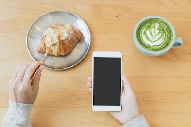 Plat leggen van de handen van een vrouw met behulp van een mobiele telefoon met een kopje groene thee latte