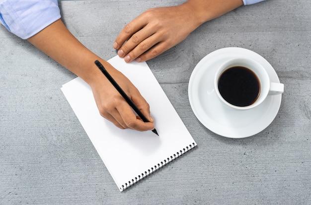 Plat leggen van de kantoorruimte met uitzicht op de handen van een man die in een notitieblok schrijft