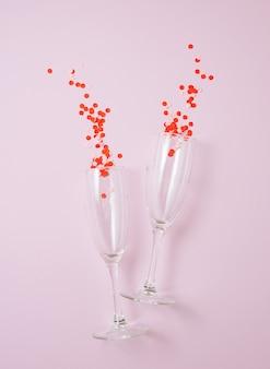 Plat leggen van de viering. twee glazen met confetti op een pastel roze achtergrond. concept van valentijnsdag, moederdag, trouwdag. bovenaanzicht