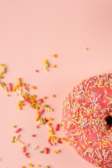 Plat leggen van donut met beglazing en kleurrijke hagelslag