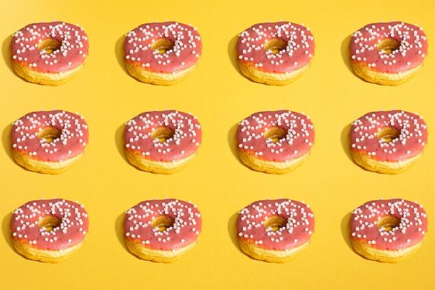 Plat leggen van donuts en schaduwen patroon op geel