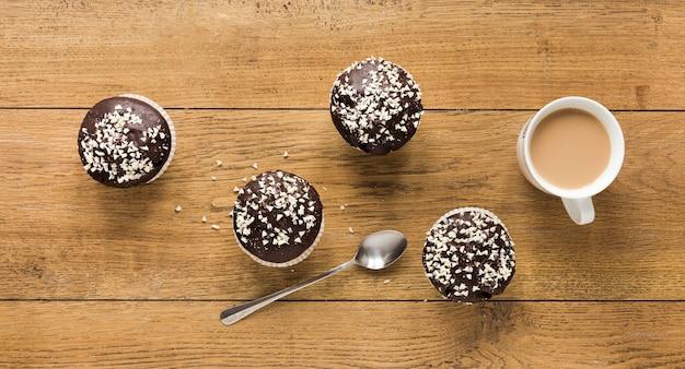 Plat leggen van donuts op houten oppervlak met koffie en lepel