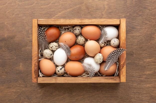 Plat leggen van doos met eieren voor pasen op houten achtergrond