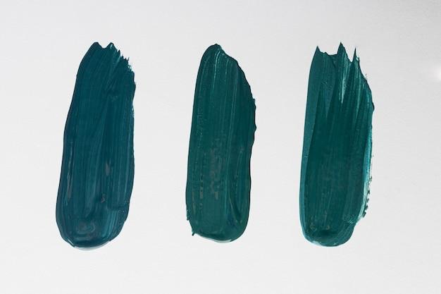 Plat leggen van drie creatieve blauwe verf penseelstreken op het oppervlak