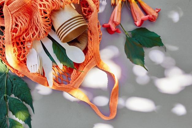 Plat leggen van eco-kraftpapier en houten serviesgoed, zomerzonlicht