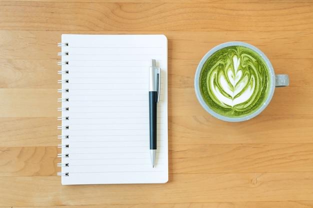 Plat leggen van een leeg notitieboekje en een kopje hete groene thee latte