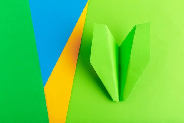 Plat leggen van een papieren vliegtuig op groene kleur