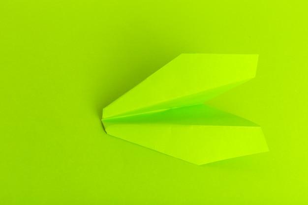 Plat leggen van een papieren vliegtuig op groene pastelkleur