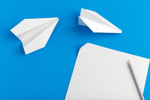 Plat leggen van een papieren vliegtuigje op een pastelblauwe achtergrond