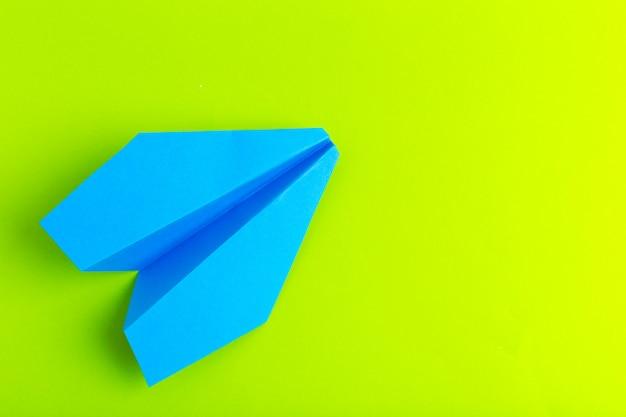 Plat leggen van een papieren vliegtuigje op groene pastel kleur achtergrond